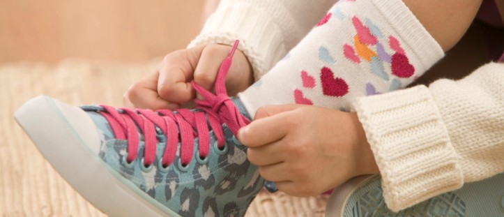 Girl Tying Her Shoelace --- Image by © Jamie Grill/Corbis
